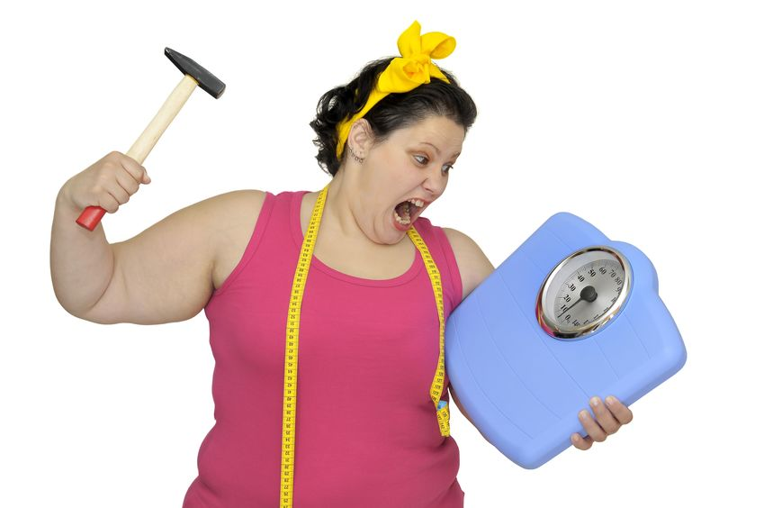 Angry woman holding scales and a hammer.