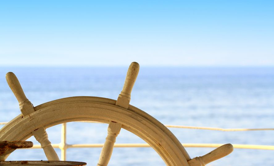 Wooden ship's wheel with blue ocean in background. Make small changes, head in a new direction.