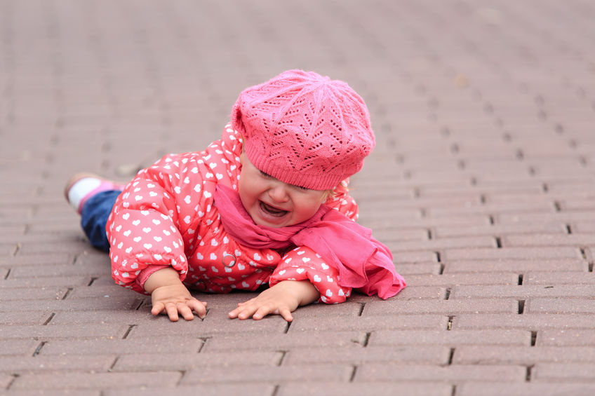 Crying baby in pink hat and coat fell down on brick walkway. Give yourself grace, get up and try again.