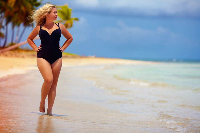Curvy blond woman in black swimsuit walking on beach. Picture your results.